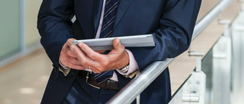 Мъж в костюм, държащ сертификат